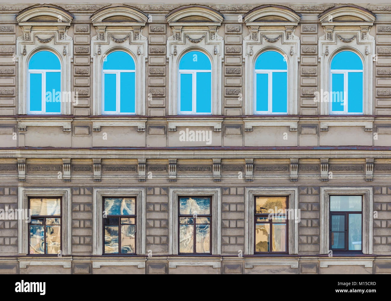 Several windows in a row on the facade of the urban historic building front view, Saint Petersburg, Russia - Stock Image