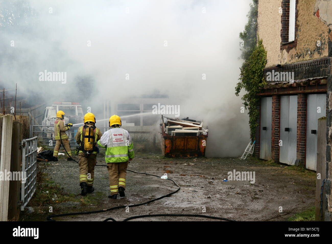 Fire Brigade attending a skip fire in North Wales - Stock Image