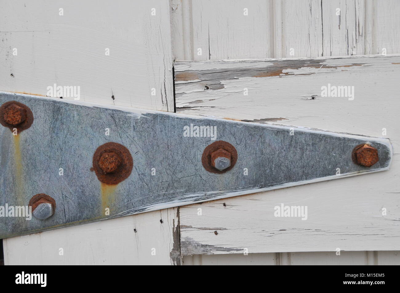 Rusted Metal Hinge on a White Barn Door Stock Photo