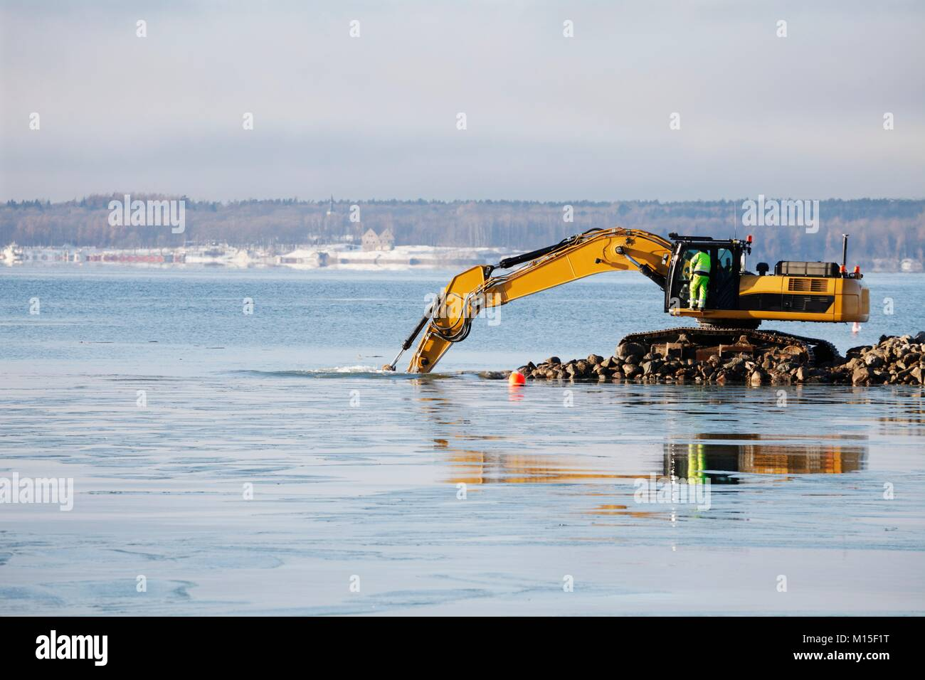 Bulldozer excavating rocks from the sea. - Stock Image