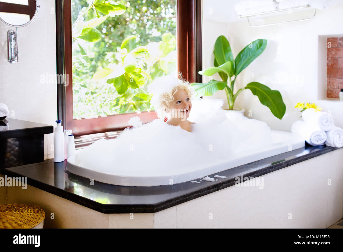 Little child taking bubble bath in beautiful bathroom with big ...