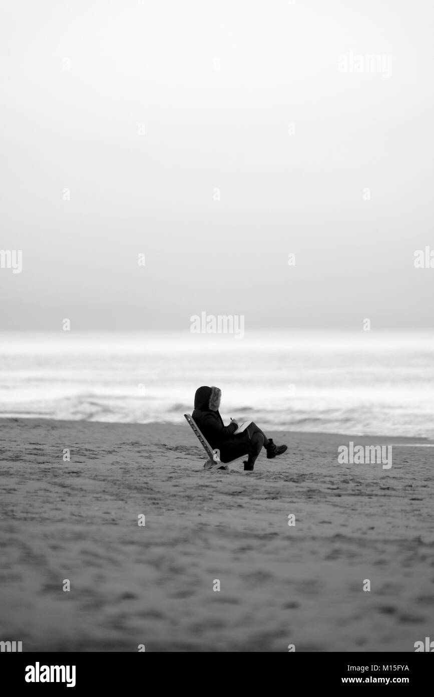 Person reading a book on the beach - Stock Image