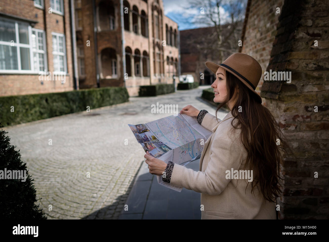 Female tourist exploring city map while standing in alley and looking on building. Traveler with smile reading geographical - Stock Image