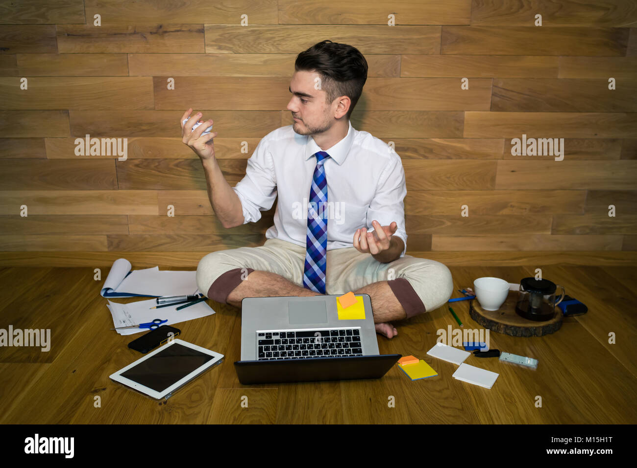 A young man in funny clothes working with project and preparing to throw out sheet with bad ideas. A barefoot businessman - Stock Image
