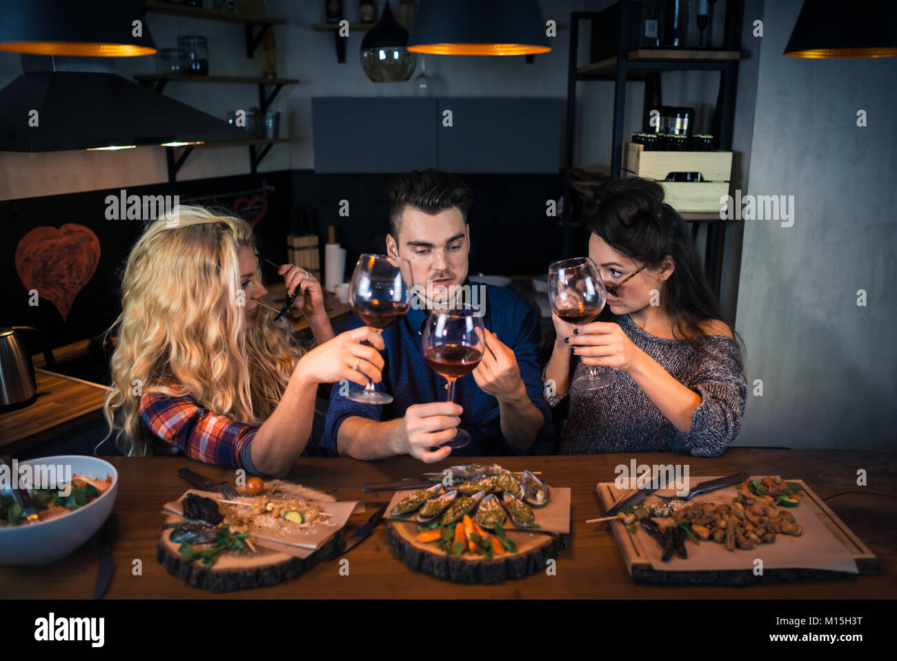 Group of friends have dinner together. Young man talks stories to friends in modern home kitchen. Happy people holds - Stock Image