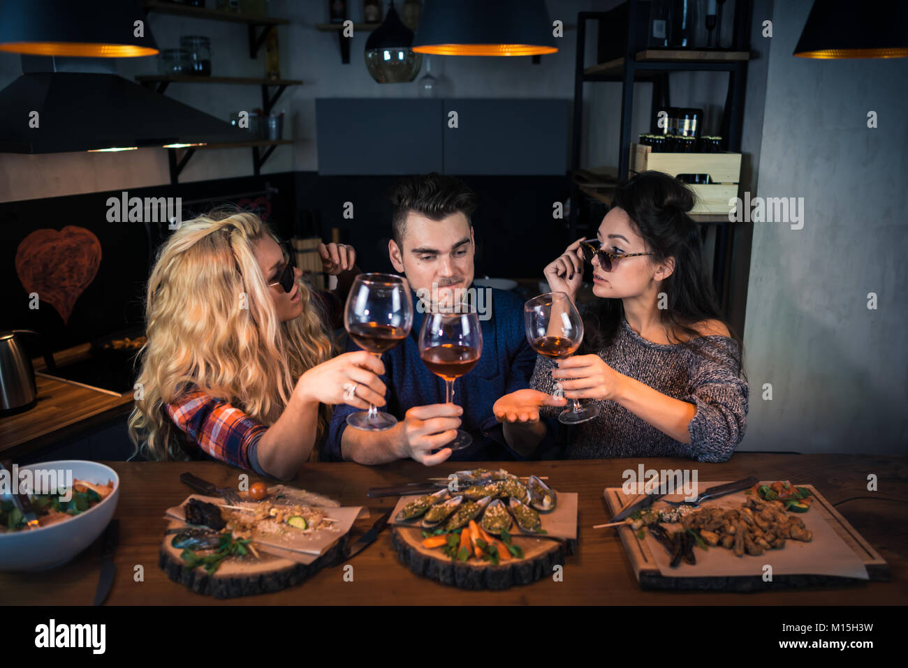 Three friends talks stories to each other in home kitchen at the bar counter. Group of attractive people has dinner - Stock Image