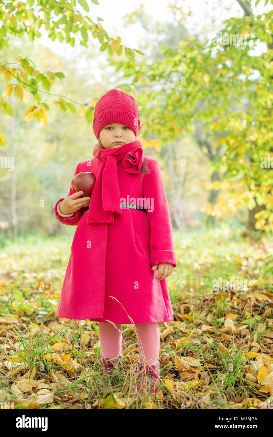 Girl in a pink coat with an apple - Stock Image