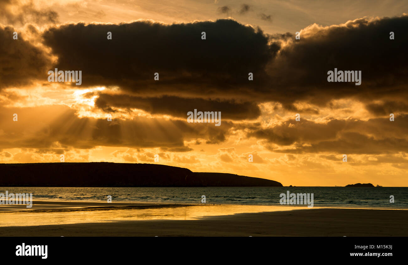 Sunbeams at sunset over the beach at Broad Haven on the Welsh coast - Stock Image