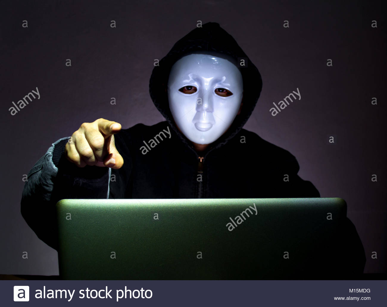 man in white mask wearing gloves and stealing computer and digital information - fraud, hacker, theft, cyber crime - Stock Image