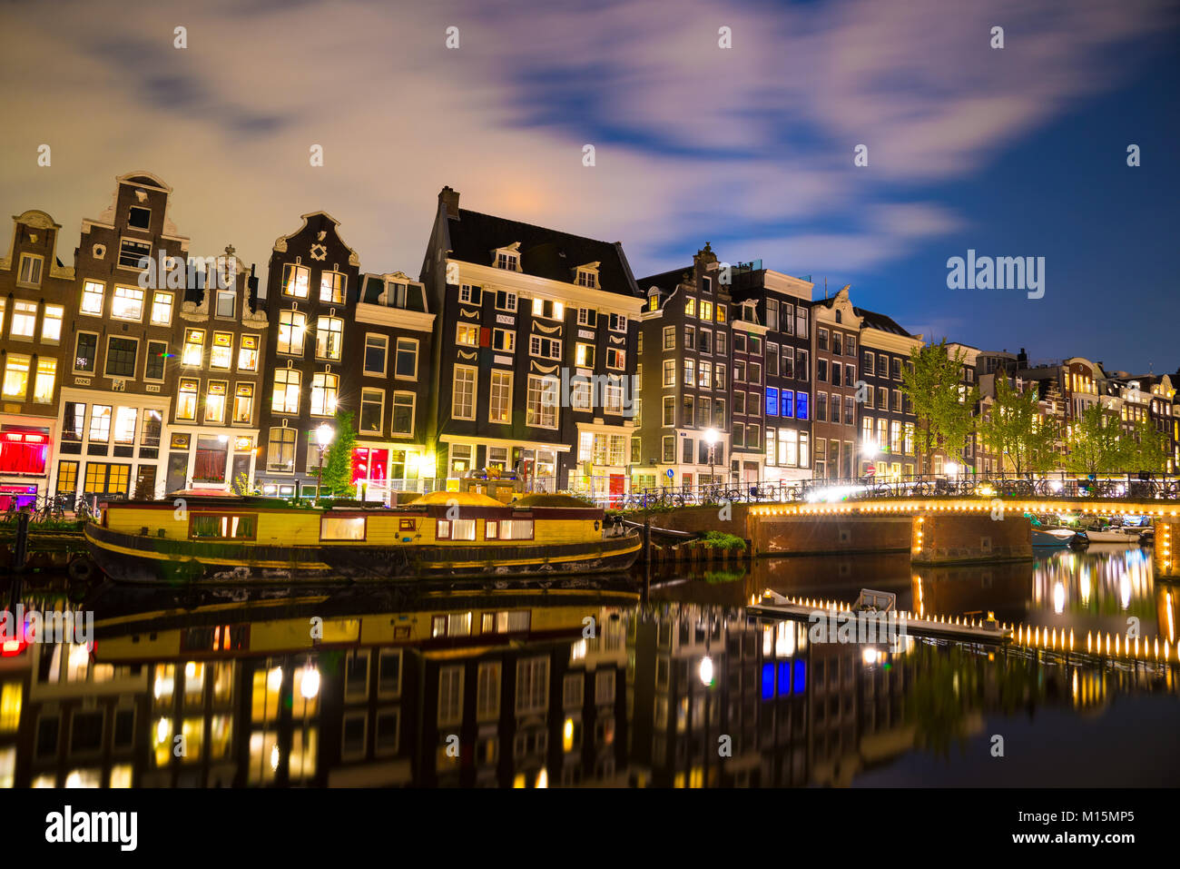 View of the Amsterdam canals and embankments along them at night. - Stock Image