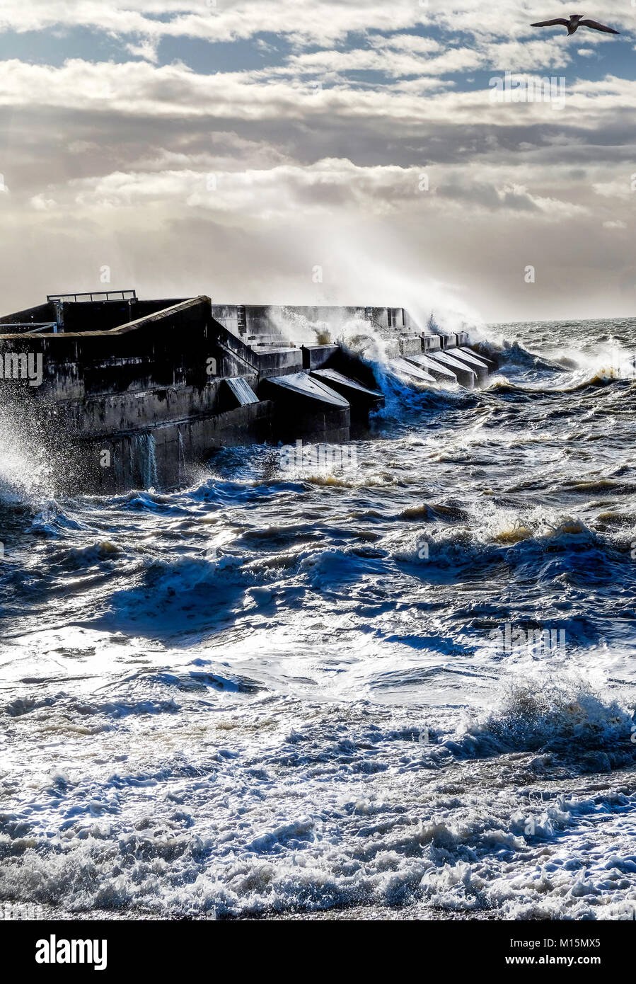 Dramatic stormy sea breaking against brighton marina black harbour wall, spray and waves high in the air, rough - Stock Image