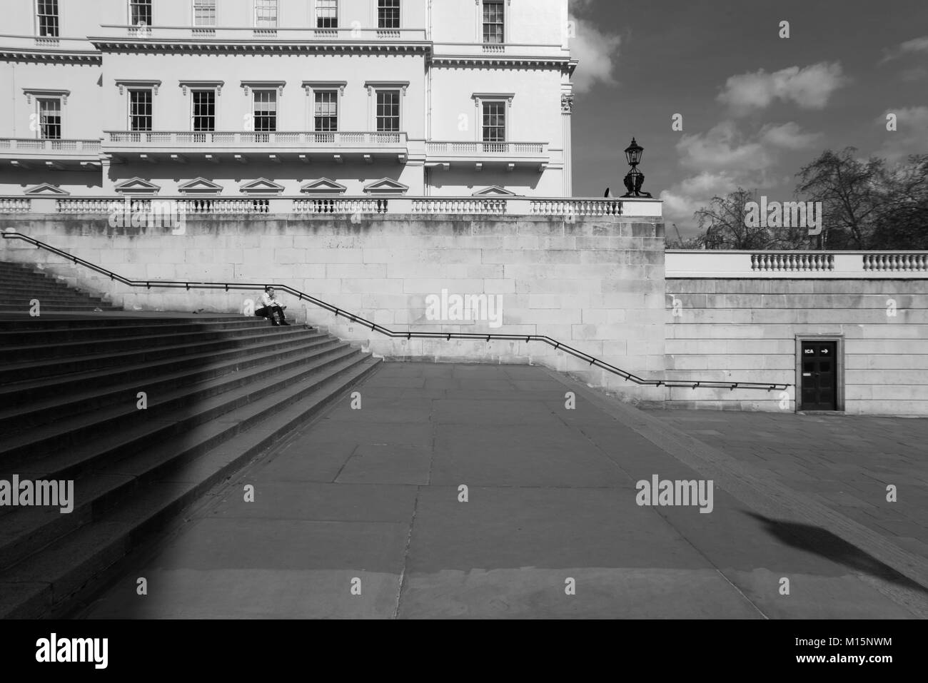 London, Duke of York Steps leading from The Mall to Waterloo Place between Carlton House Terraces. Man sits quietly - Stock Image