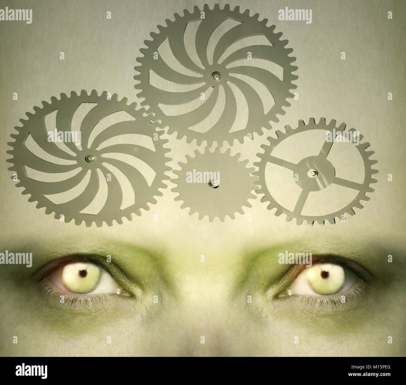 Human eyes with gearing on the forehead representing an abstract concept of the complexity of the human mind - Stock Image