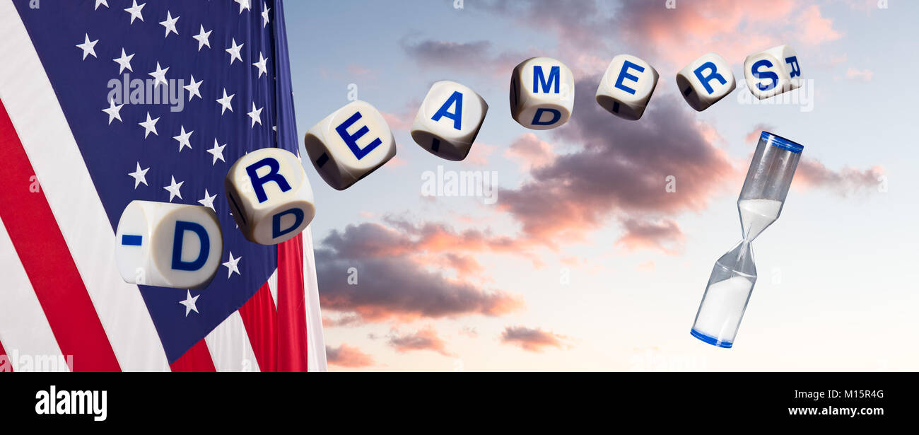 Dreamers in spelling letters against sunset sky and flag and hourglass - Stock Image