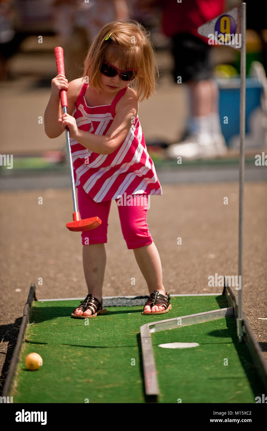 A little girl putting a golf ball at mini golf green - Stock Image