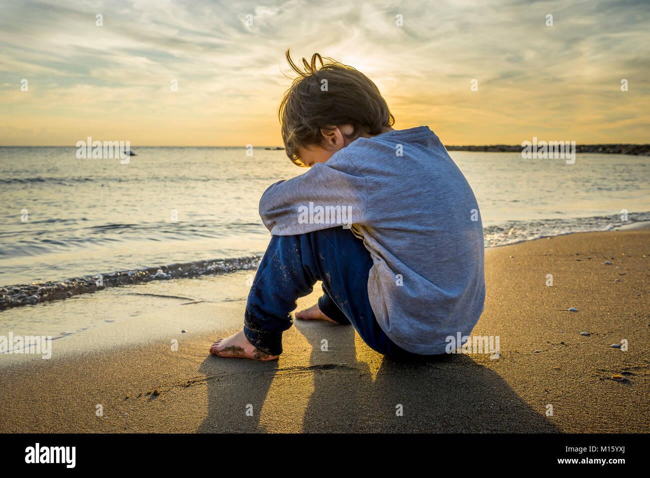 Sad boy sitting on the beach stock image