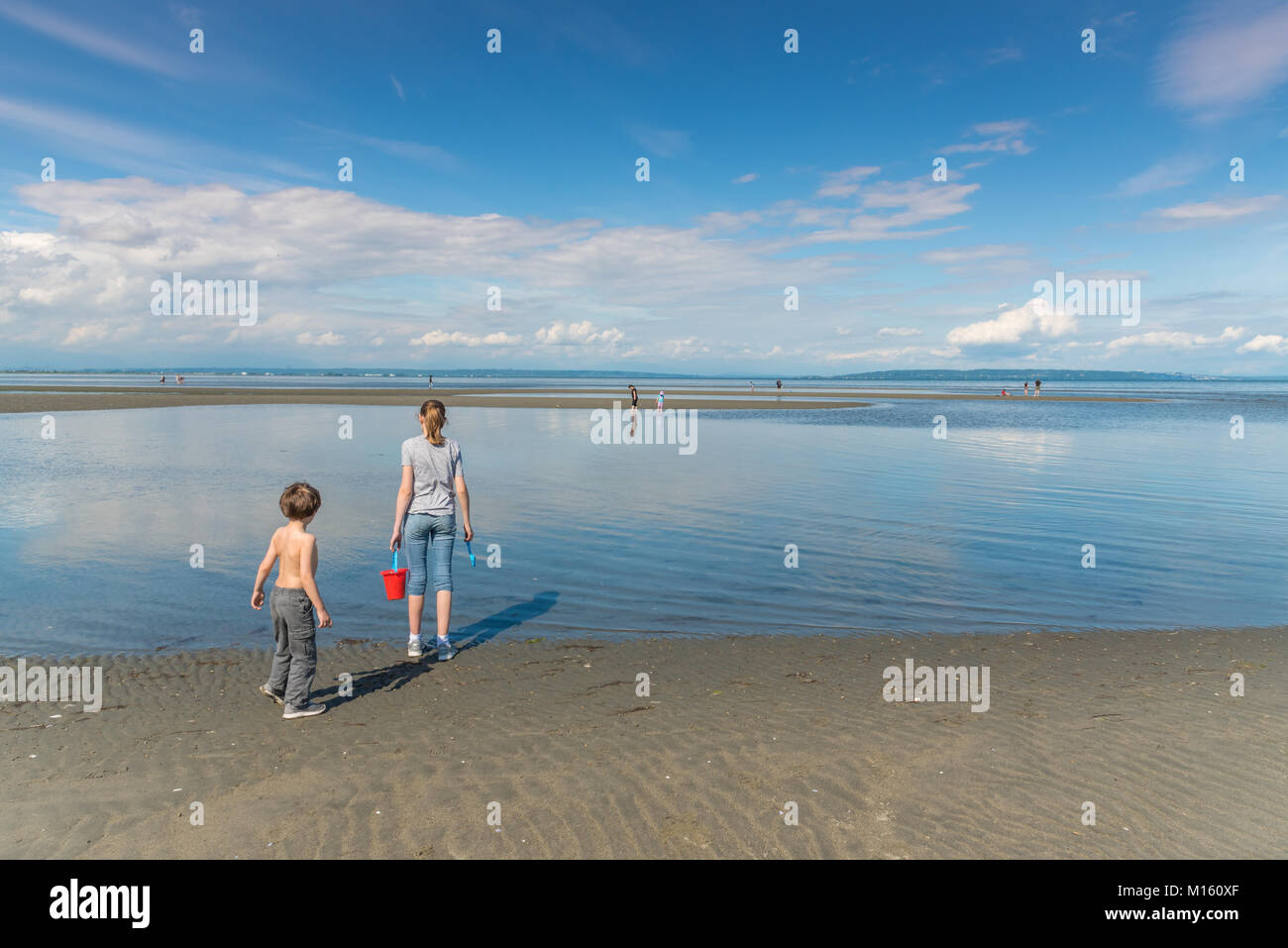 Young families and children love to explore the extensive tide pools during low tide at Centennial Beach in Delta, - Stock Image