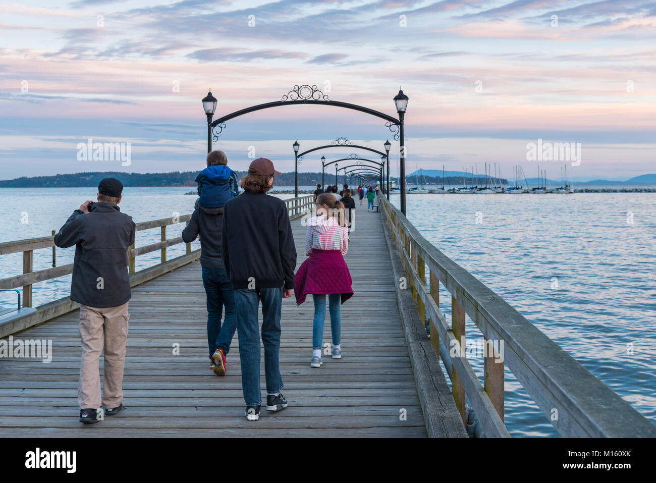 A family walks down the White Rock Pier at sunset. The pier, built in the 1920's, is a popular tourist attraction. Stock Photo
