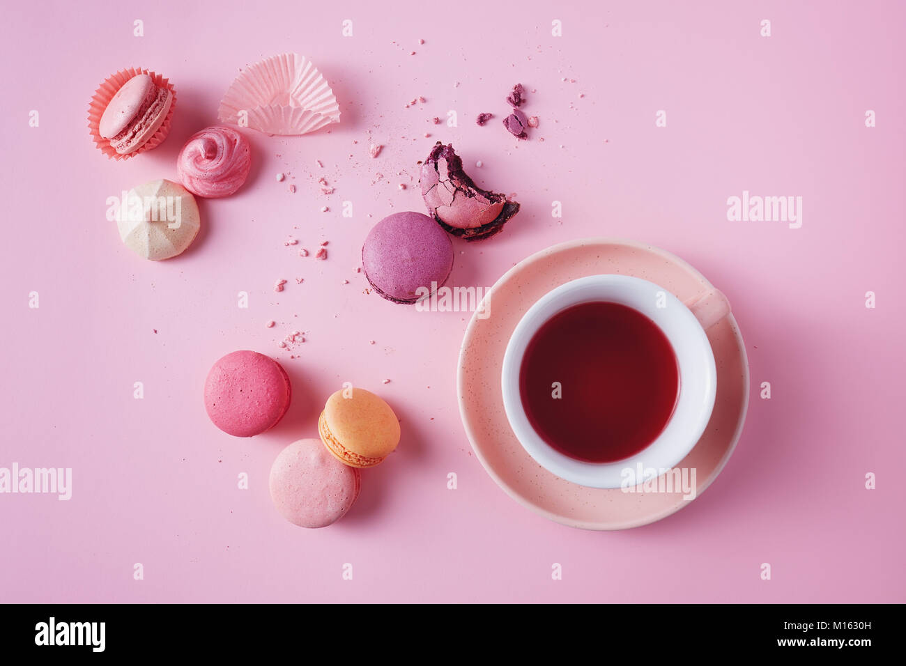 Sweet french macarons and meringues on pink background. - Stock Image