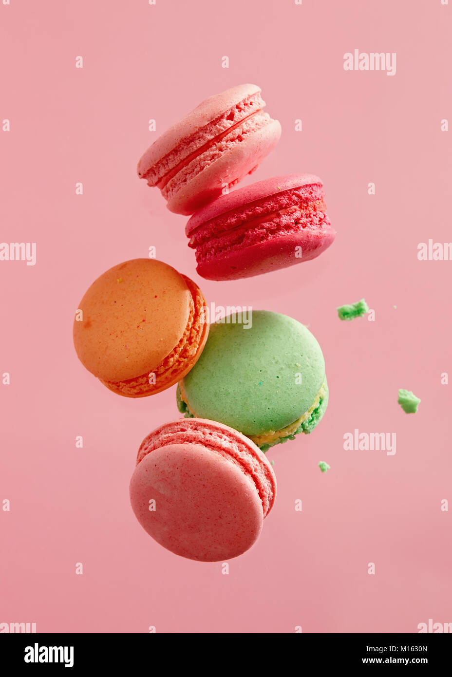 Different types of macaroons in motion falling on pink background. Sweet and colourful french macaroons falling - Stock Image