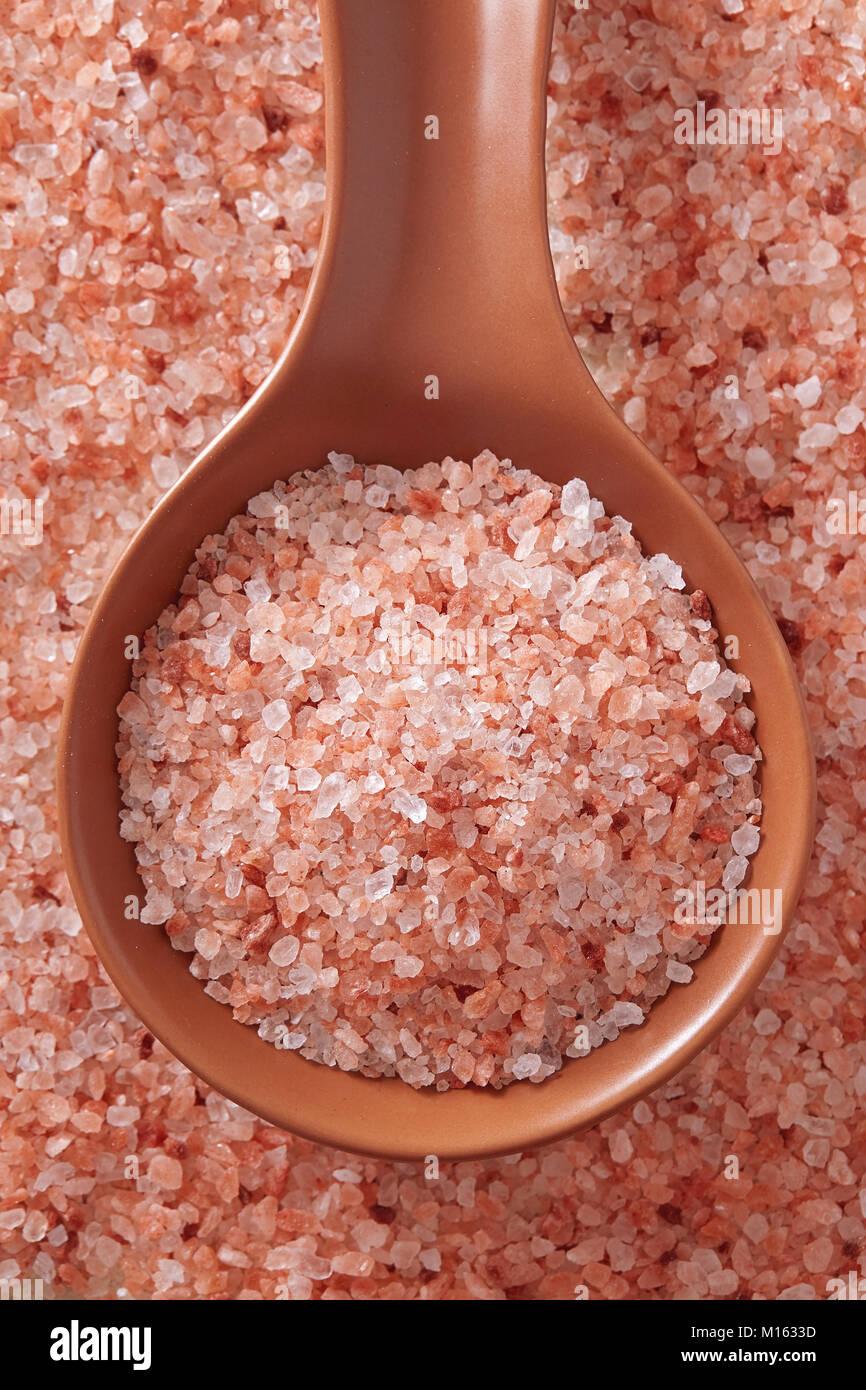 Pink Himalayan salt in spoon. Top view of spoon full of pink Himalayan salt on salt crystal. Stock Photo