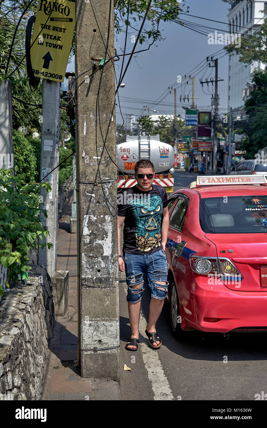 Thailand street with pavement blocked by power supply post forcing pedestrians into the busy road and a dangerous - Stock Image