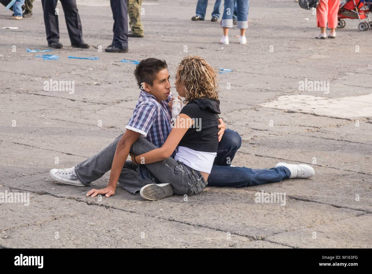 Young couple in love sitting in a public square in Mexico City. - Stock Image