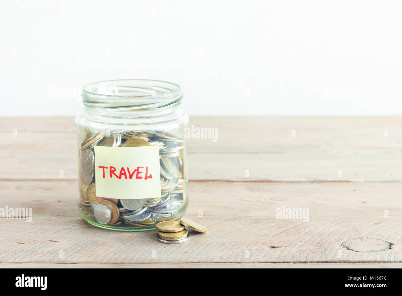 Coins in glass jar with red heart and Travel label. Money savings, plans and dreams concept, copy space. Stock Photo