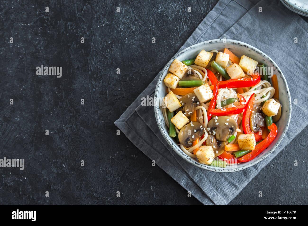 Stir fry with udon noodles, tofu, mushrooms and vegetables. Asian vegan vegetarian food, meal, stir fry over black - Stock Image