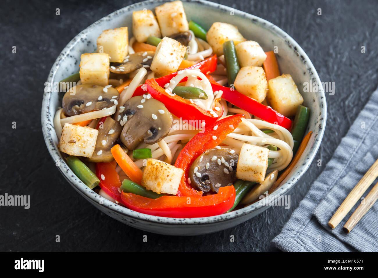 Stir fry with udon noodles, tofu, mushrooms and vegetables. Asian vegan vegetarian food, meal, stir fry over black Stock Photo