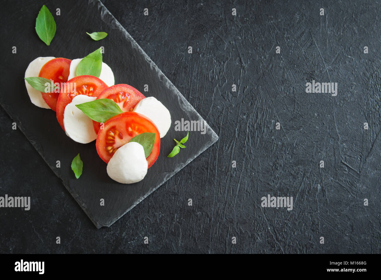 Traditional Italian Caprese Salad - sliced tomatoes, mozzarella cheese and basil on dark stone background, top view, - Stock Image