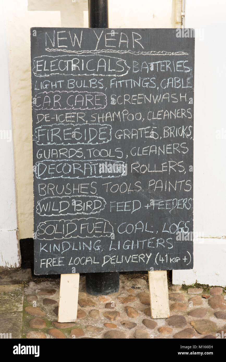 A chalkboard sign outside a traditional ironmongers shop advertising a wide range of goods for sale - Stock Image