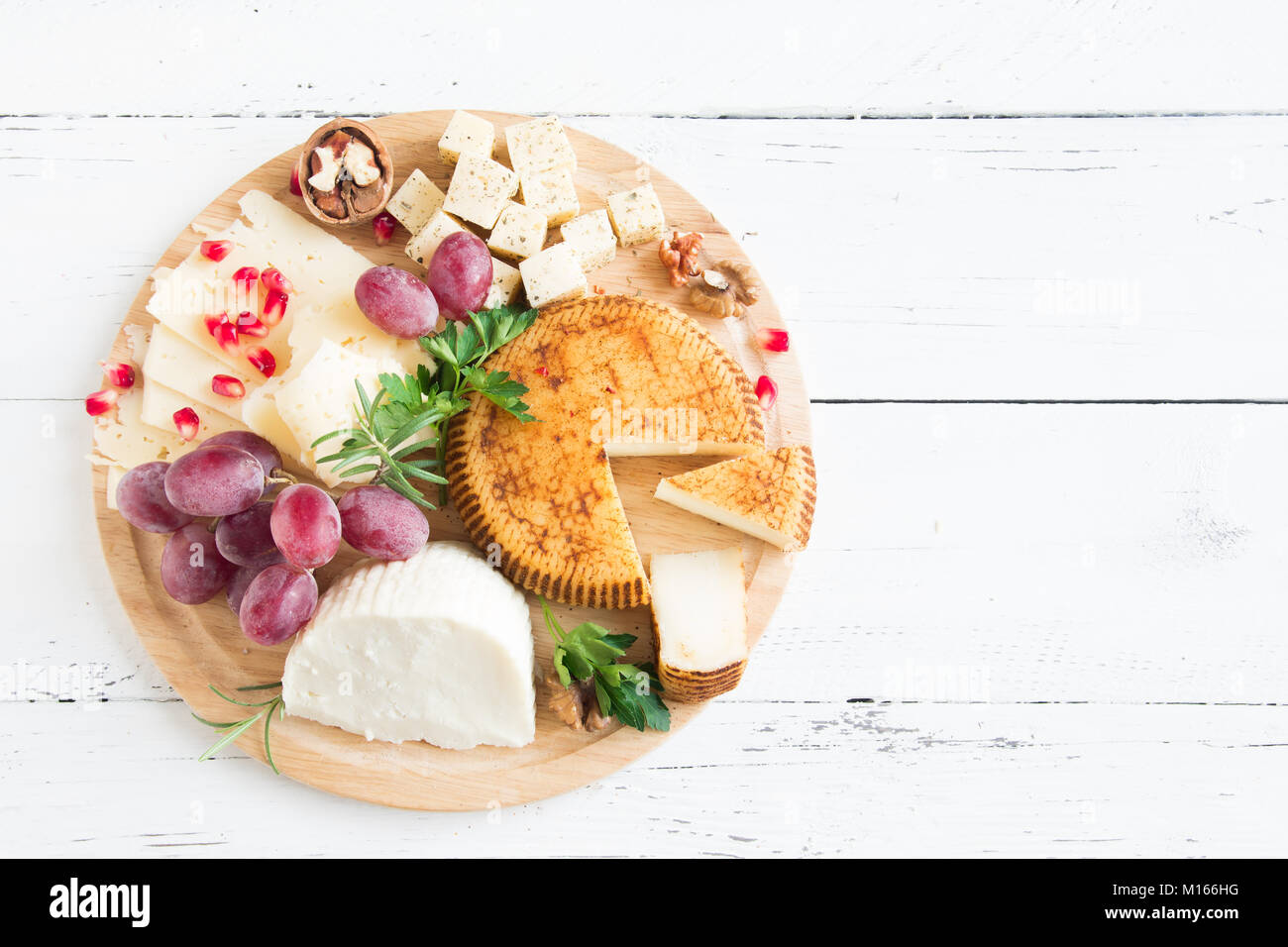 Cheese platter with assorted cheeses, grapes, nuts over white wooden background, copy space. Italian cheese and - Stock Image