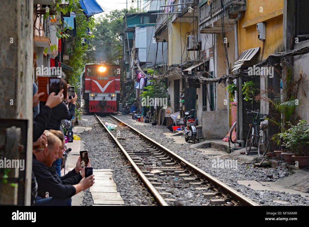 Hanoi, Vietnam - 16th December 2017. Tourists take photos of 15.30 train from Hanoi to Sapa as it goes along a residential Stock Photo