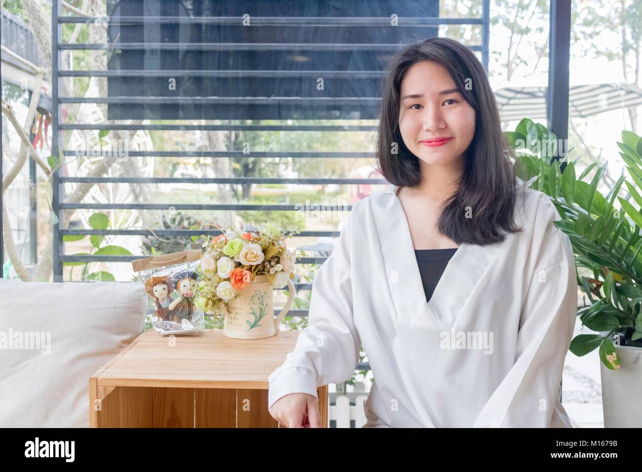 An Asian girl in white coat sitting and smiling in the glass room of vintage cafe in Bangkok, Thailand January 3,2017 - Stock Image