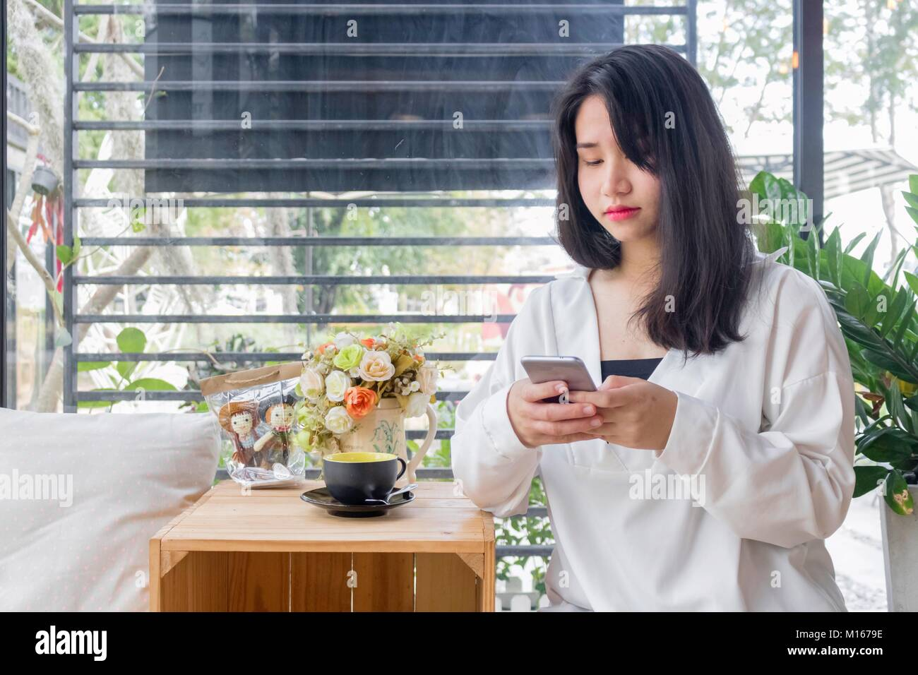 An Asian girl in white coat sitting and playing mobile phone in the glass room of vintage cafe in Bangkok, Thailand - Stock Image