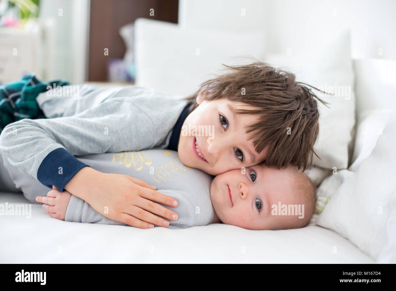 Two children, baby and his older brother in bed in the morning, playing together, laughing and having a good time, - Stock Image
