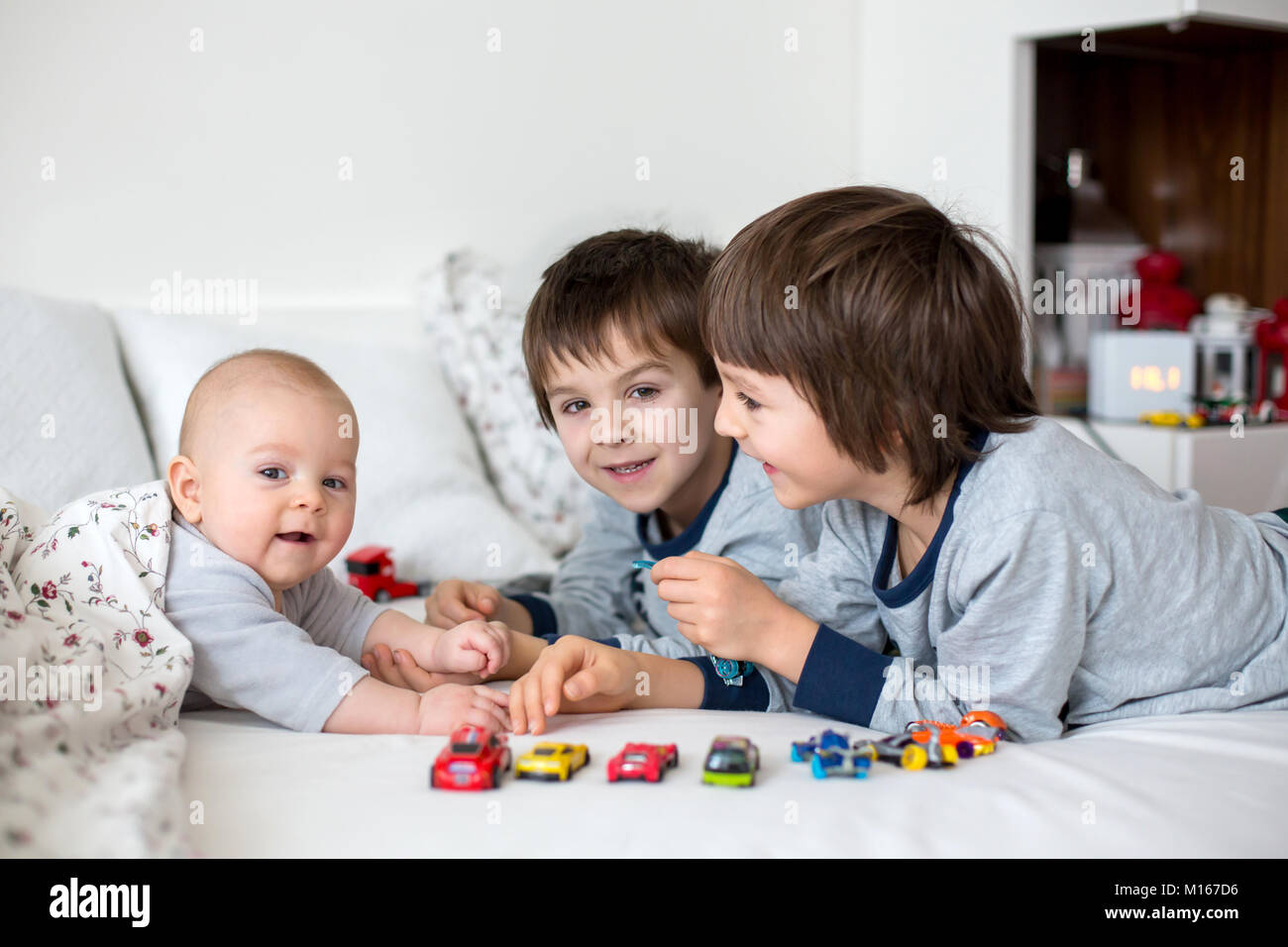 Three children, baby and his older brothers in bed in the morning, playing together, laughing and having a good - Stock Image