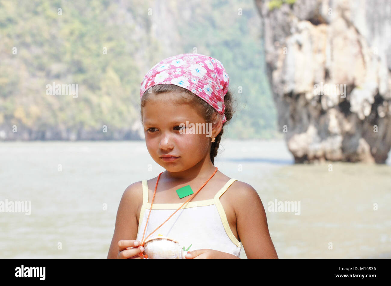 small tan girl in scarf on a beach hot - Stock Image