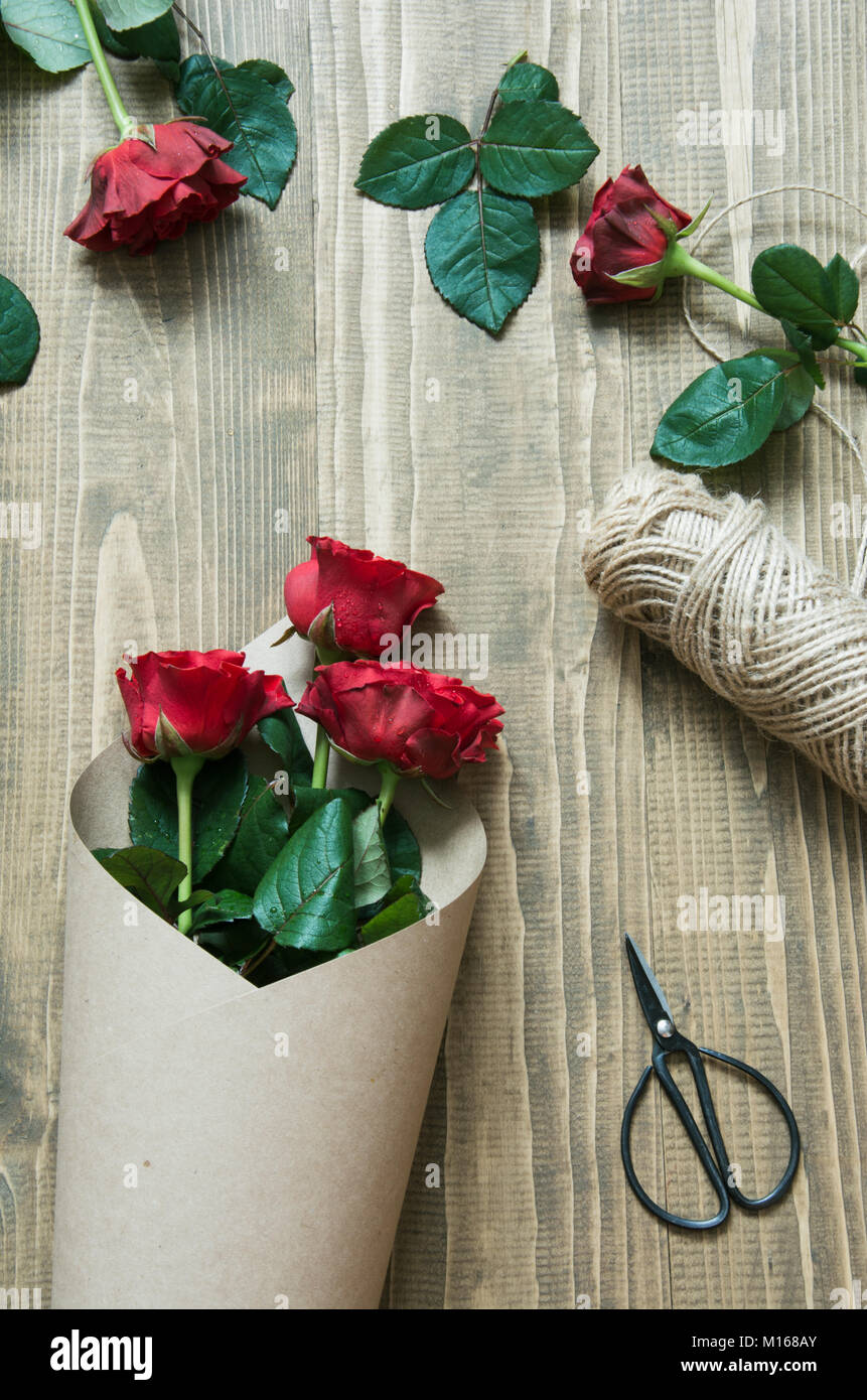 Florist Making A Red Roses Bouquet Wrapping In Kraft Paper On A