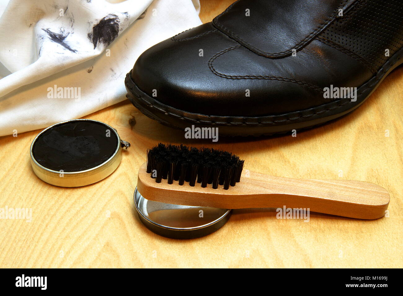 Partial view of a shoe with cleaning rag, shoe polish and brush. - Stock Image