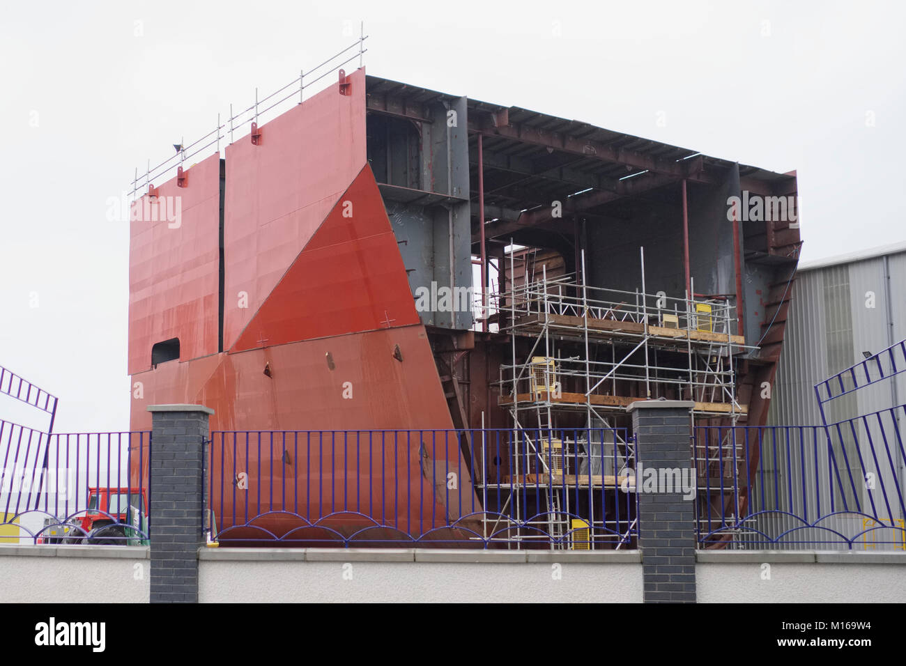 Shipbuilding in progress with scaffold around large steel vessel - Stock Image