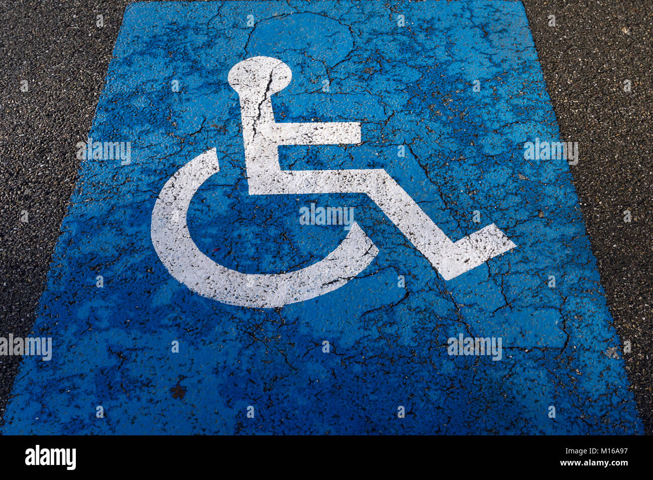 Sign for parking for people with disabilities on torn tar, Alsace, France Stock Photo