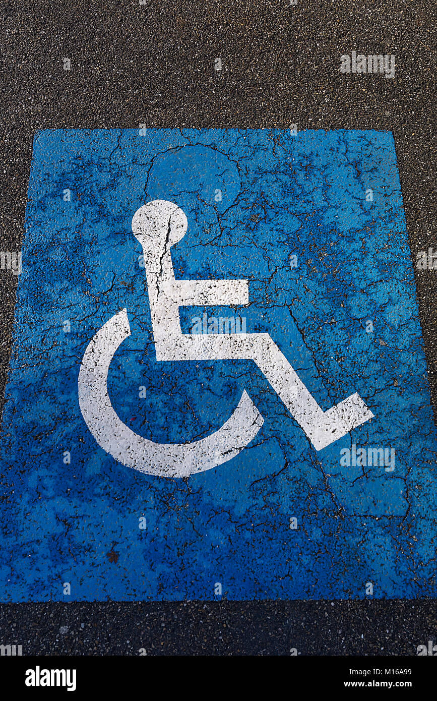 Sign for parking for people with disabilities on torn tar, Alsace, France - Stock Image