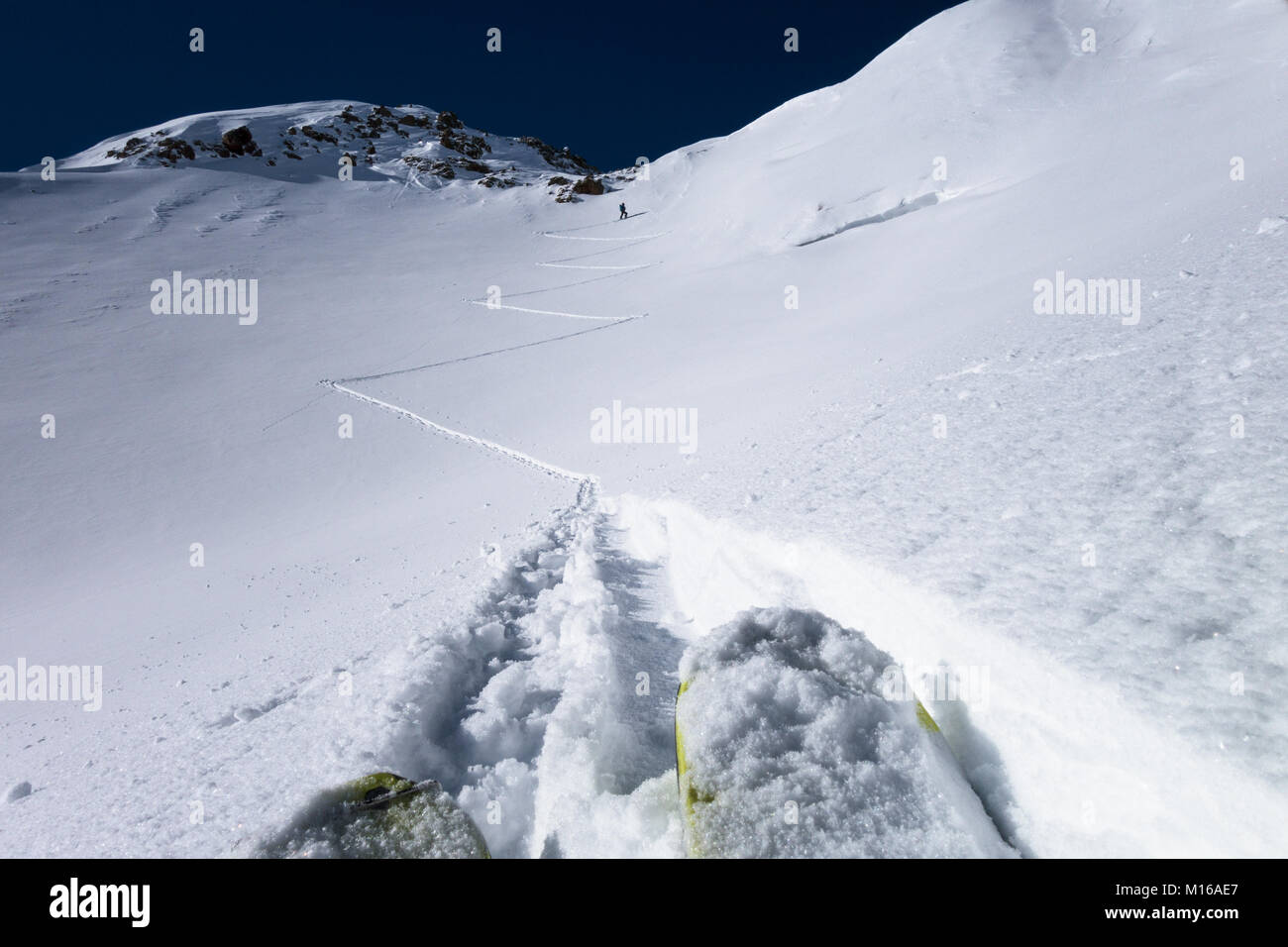 One skier following a leader making switchback turns up steep winter powder snow slope leading to alpine mountain Stock Photo