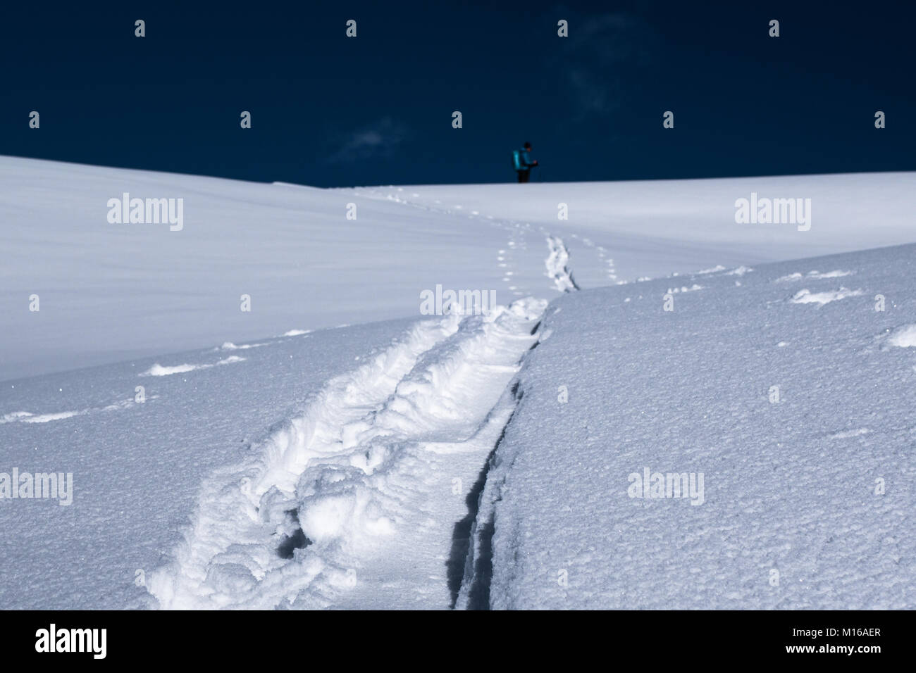 A shallow depth picture of track in new powder snow made by ski tourer waiting on the ridge ahead Stock Photo