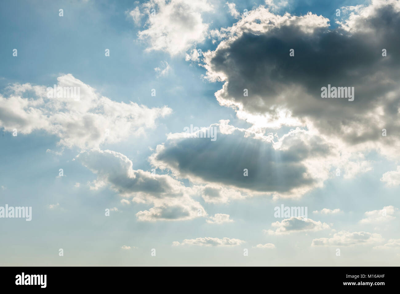 Sun shines behind dark clouds, Germany - Stock Image