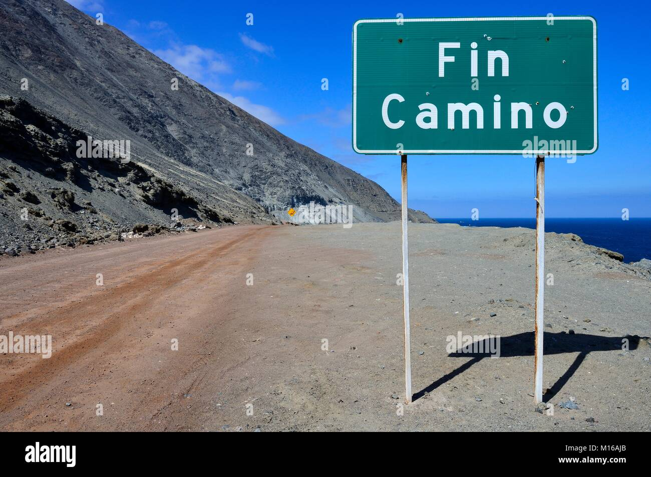 Warning sign at the end of the road on the rocky coast, near Antofagasta, Región de Antofagasta, Chile - Stock Image