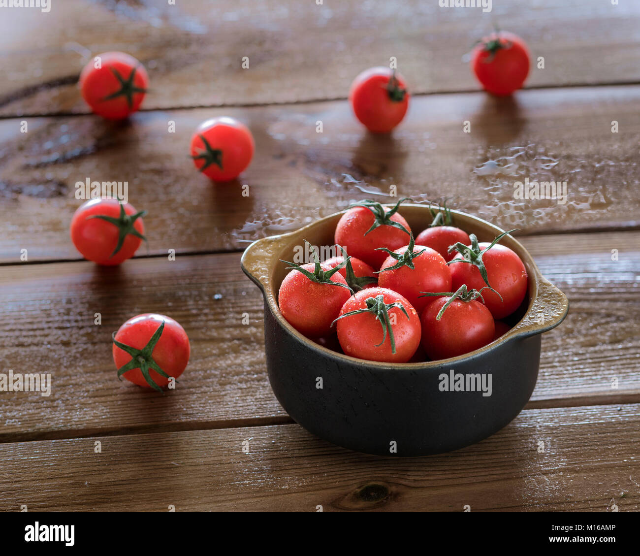 Cocktail tomatoes sprayed with water in brown bowl on wooden table - Stock Image