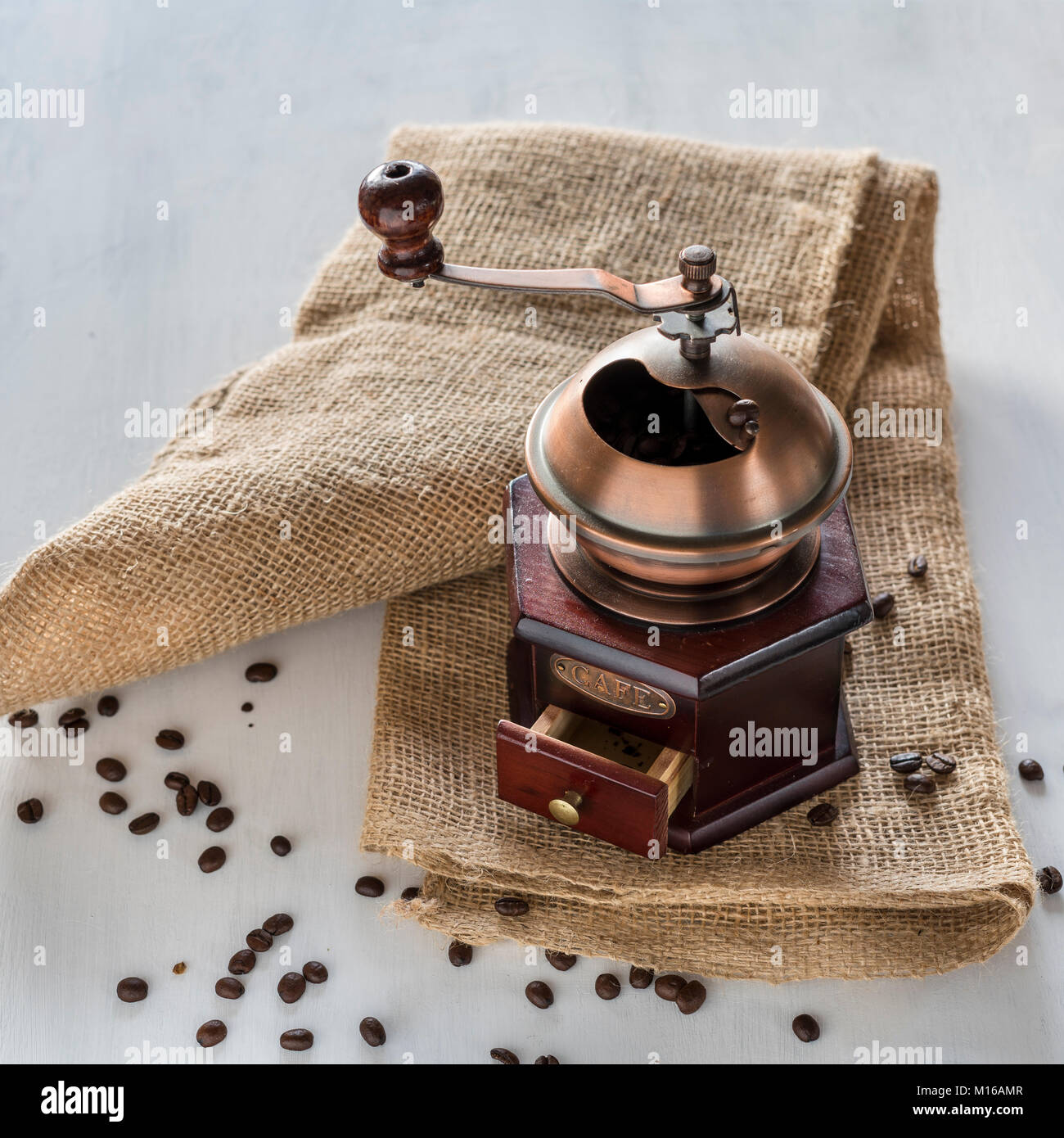 Old coffee grinder on jute bag, coffee beans on white ground - Stock Image